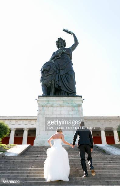 bridal couple walking up the steps to statue of Bavaria while sunny day