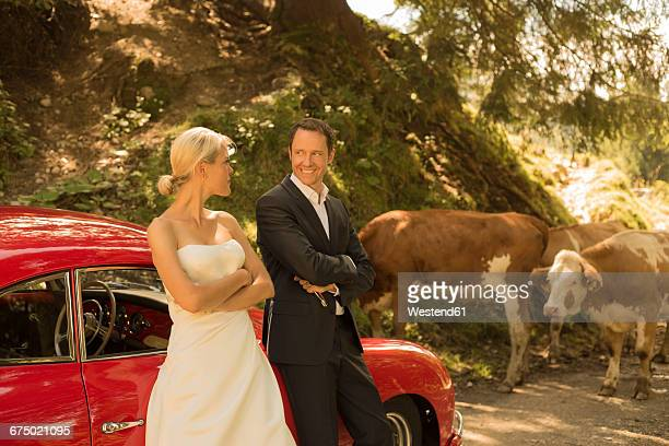 Bridal couple with vintage car waiting on a dirt track