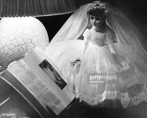 A bridal doll by Madame Alexander wears a roman­tic cloud of tulle and lace and carries a petite be ribboned bouquet of posies Credit Denver Post Inc