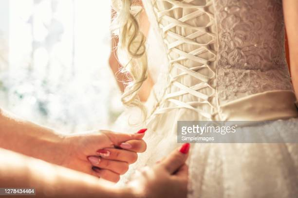 bridal dress corset laces being tightened during a wedding preparation. - satin dress stock pictures, royalty-free photos & images