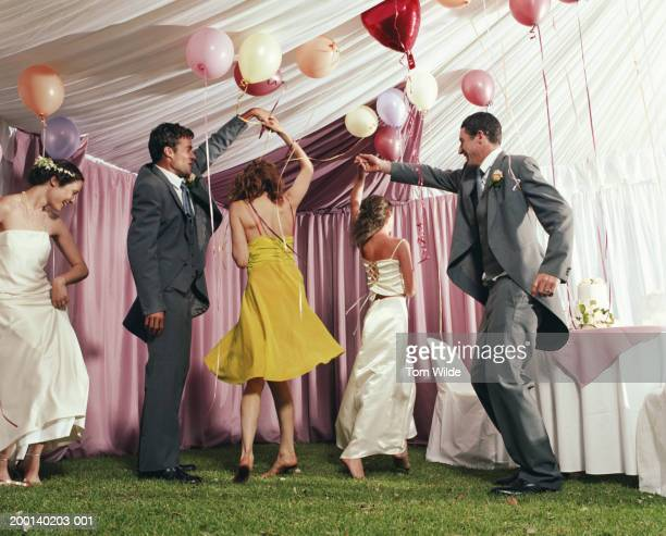 bridal party dancing in marquee - wedding guest stock pictures, royalty-free photos & images