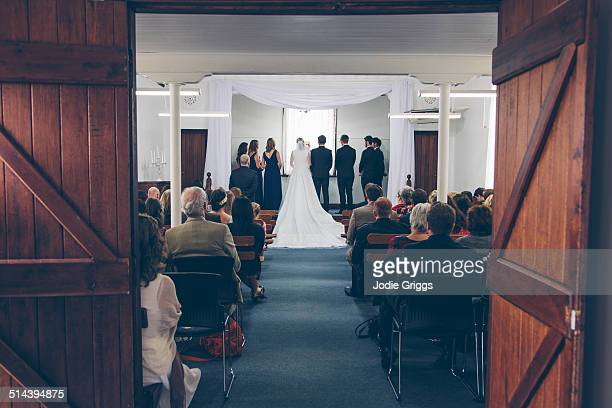 bridal party standing on stage in small hall - wedding ceremony stock pictures, royalty-free photos & images