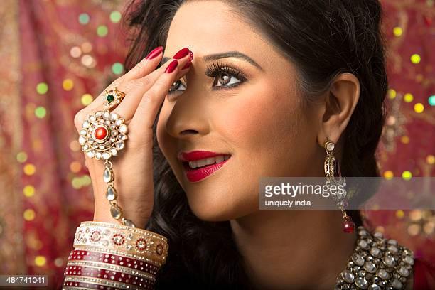 Bridal woman putting on bindi on her forehead