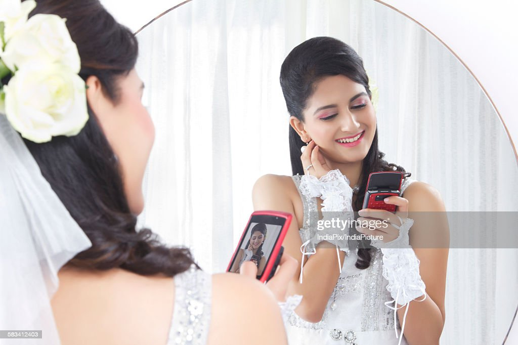 Bride admiring her own photograph : Stock Photo