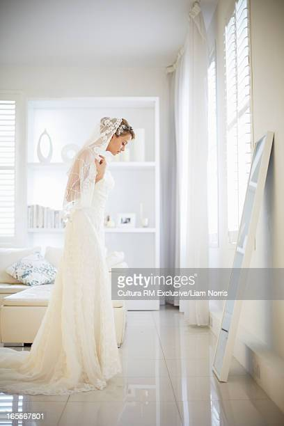 Bride admiring herself in dress and veil