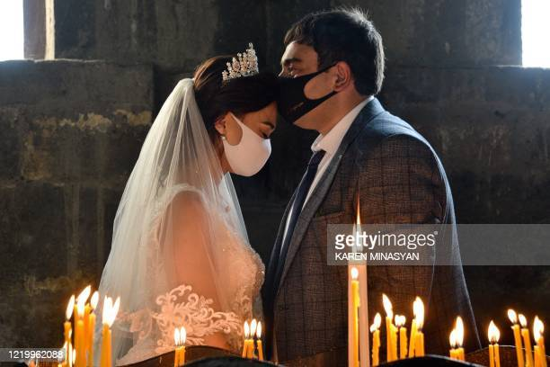 Bride and a bridegroom wearing protective face masks exchange kisses during a wedding ceremony in a church in the Saghmosavan village outside Yerevan...