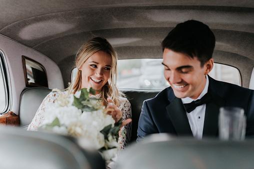 Bride and bridegroom in backseat of car - gettyimageskorea
