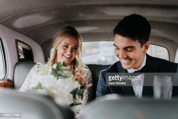 bride and bridegroom in backseat of car - matrimonio foto e immagini stock