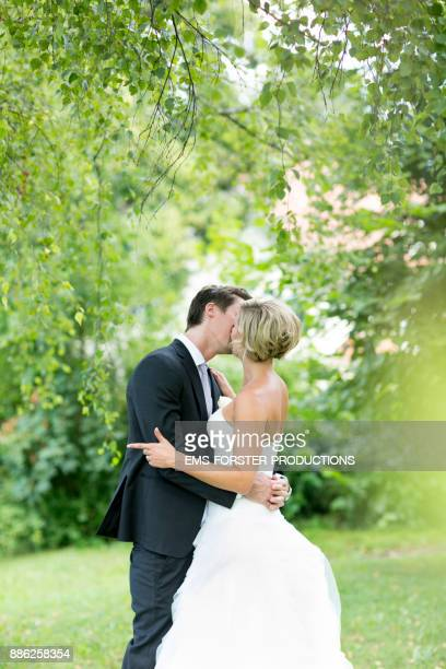 bride and bridegroom kissing outside after wedding ceremony