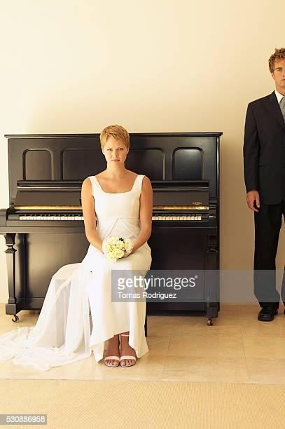 Bride and bridegroom sitting near upright piano