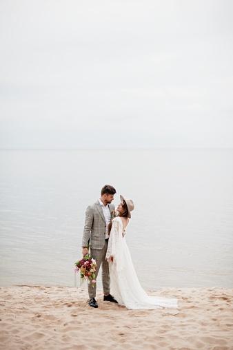 Bride And Bridegroom Standing At Beach During Wedding Ceremony - gettyimageskorea