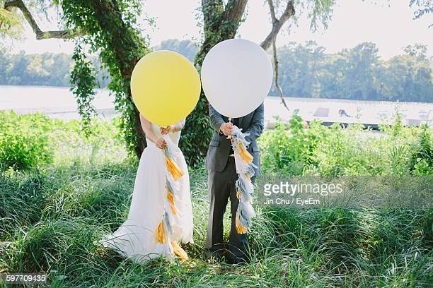 Bride And Bridegroom Standing With Balloons In Front Of Face On Grass
