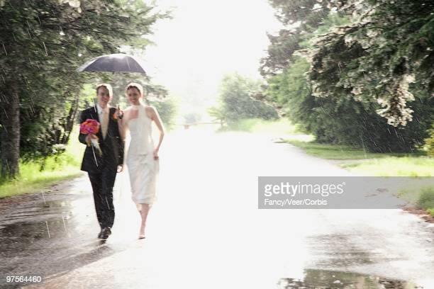 Bride and bridegroom walking through rain