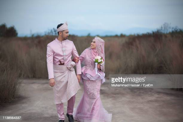 Bride And Bridegroom Wearing Traditional Clothing On Field