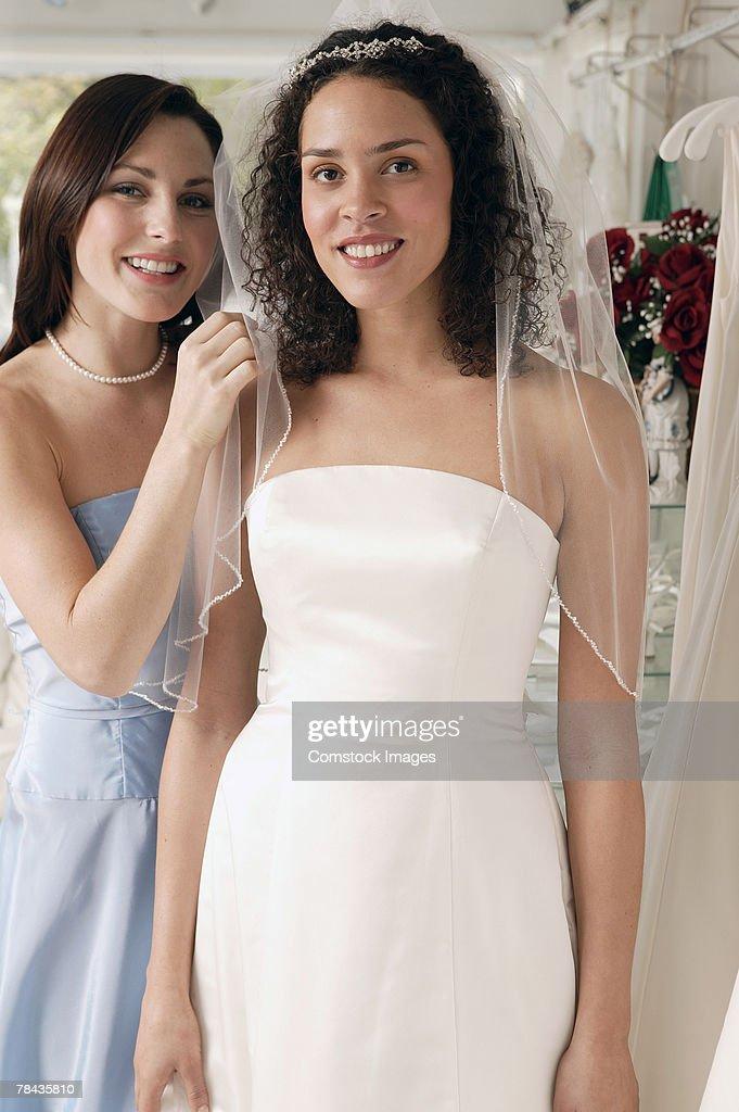 Bride and bridesmaid in bridal shop : Stockfoto