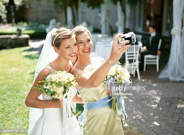 Bride and bridesmaid photographing themselves, smiling