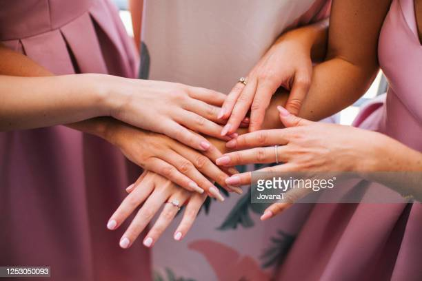 bride and bridesmaids holding their hands together - satin dress stock pictures, royalty-free photos & images