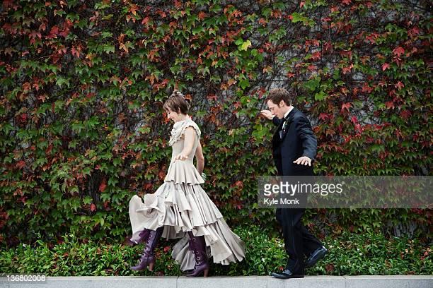 Bride and broom walking on ledge