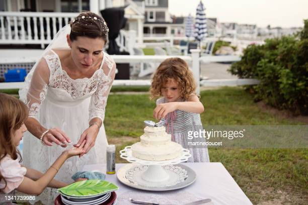 """bride and daughters decorating the cake at small wedding celebrations. - """"martine doucet"""" or martinedoucet stock pictures, royalty-free photos & images"""