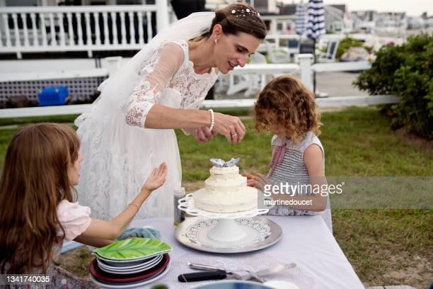 "bride and daughters decorating the cake at small wedding celebrations. - ""martine doucet"" or martinedoucet imagens e fotografias de stock"
