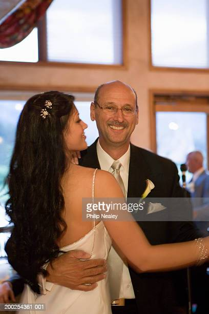 Bride and father dancing at wedding, smiling