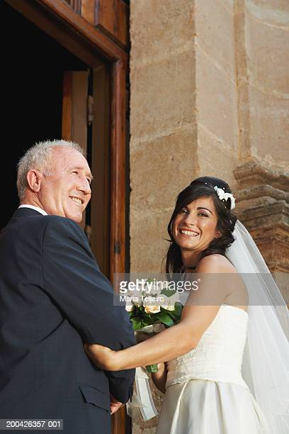 Bride and father entering church, smiling, portrait