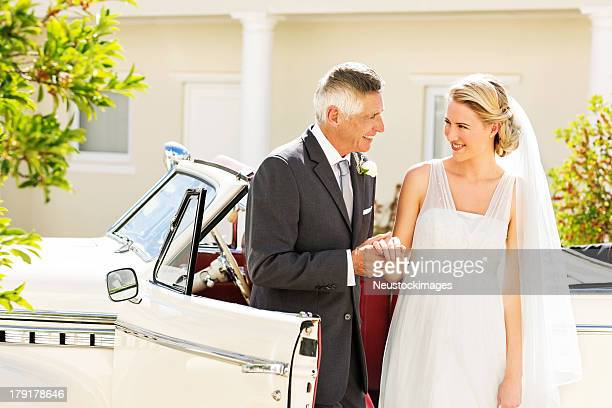 Bride And Father Holding Hands By Car