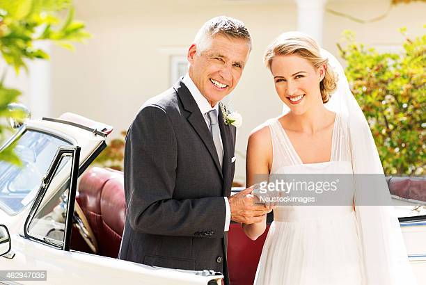 Bride And Father Holding Hands While Standing By Car