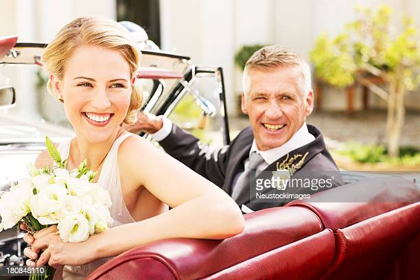 Bride And Father Looking Away While Sitting In Car