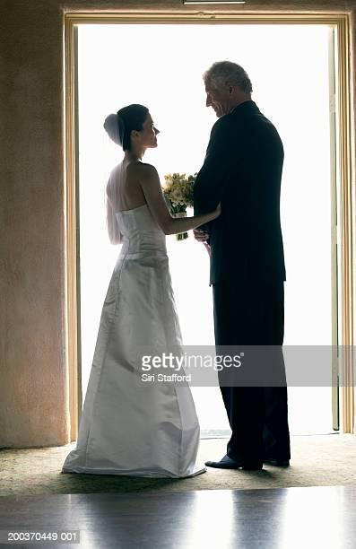 Bride and father standing in doorway