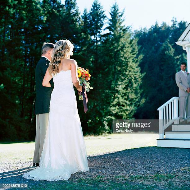 bride and father standing outside chapel, groom standing in background - chapel stock pictures, royalty-free photos & images