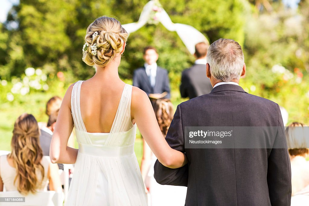 Bride And Father Walking Down The Aisle During Outdoor Wedding : Stock Photo