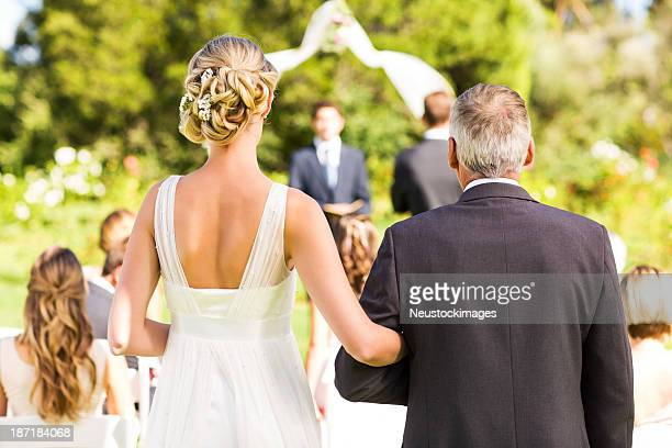 bride and father walking down the aisle during outdoor wedding - wedding ceremony stock photos and pictures
