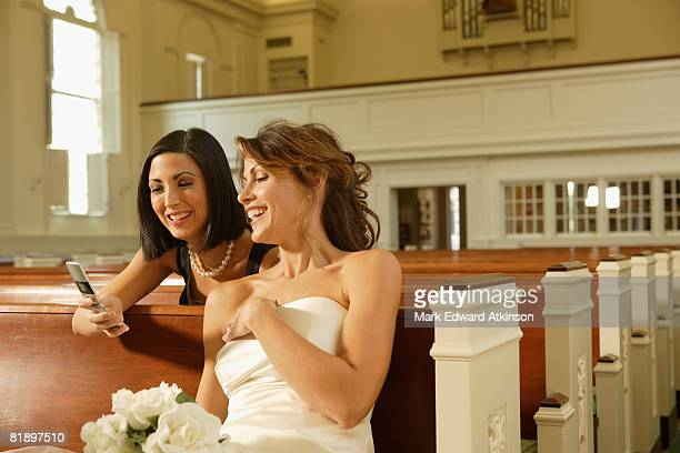 Bride and friend looking at cell phone