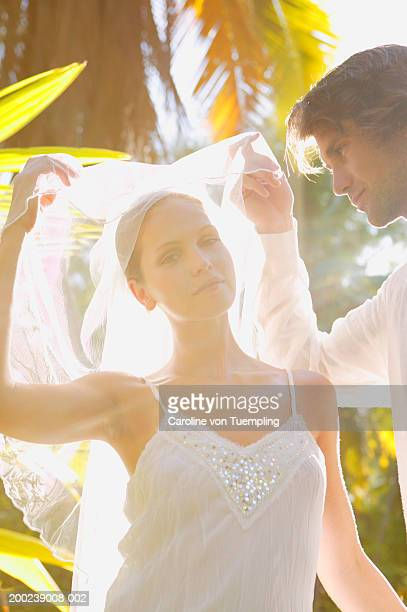 Bride and groom adjusting veil in forest