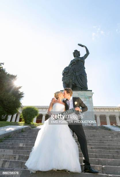 bride and groom are kissing in fron of the Bavaria statue in Munich after wedding ceremony holding a registration plate with 'just married' letters on it