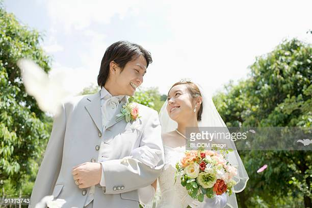 Bride and groom arm in arm in flower shower, smiling at each other