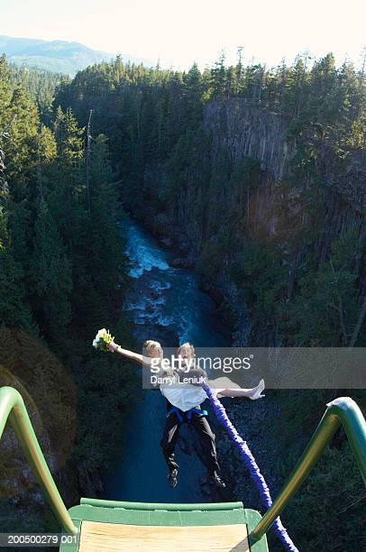 Bride and groom bungee jumping, elevated view, (wide angle)