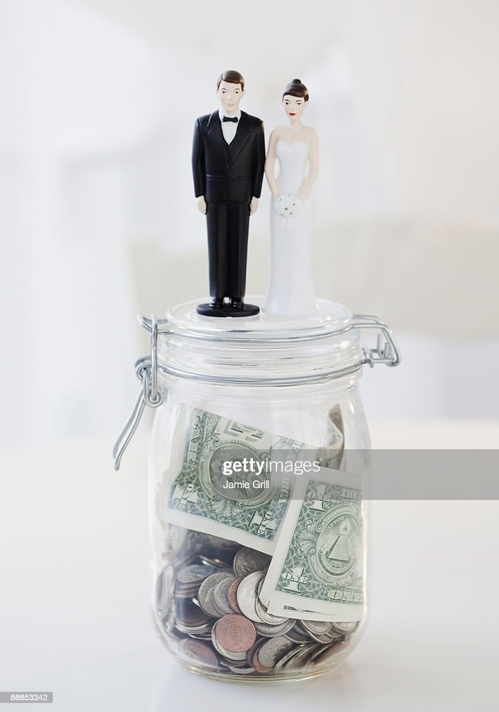 Bride and groom cake toppers on jar of money : Stock Photo