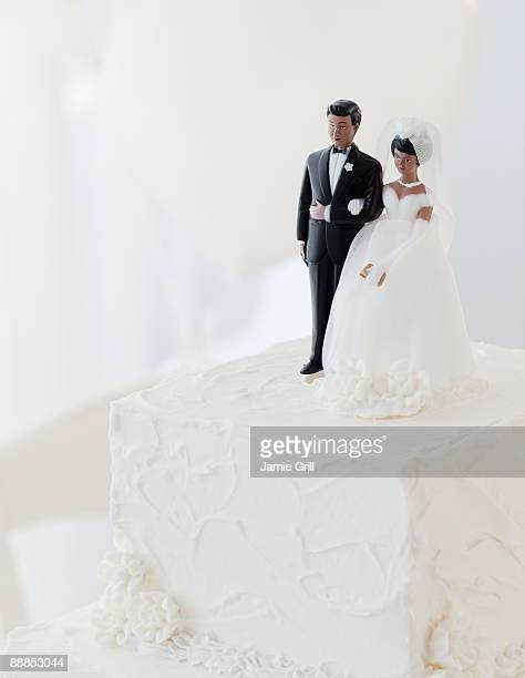bride and groom cake toppers on wedding cake - wedding cake figurine stock pictures, royalty-free photos & images