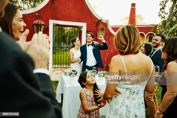 bride and groom celebrating while cutting cake during outdoor wedding reception - invité photos et images de collection