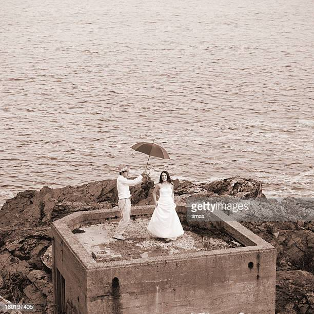 Bride and groom dancing on concrete bunker