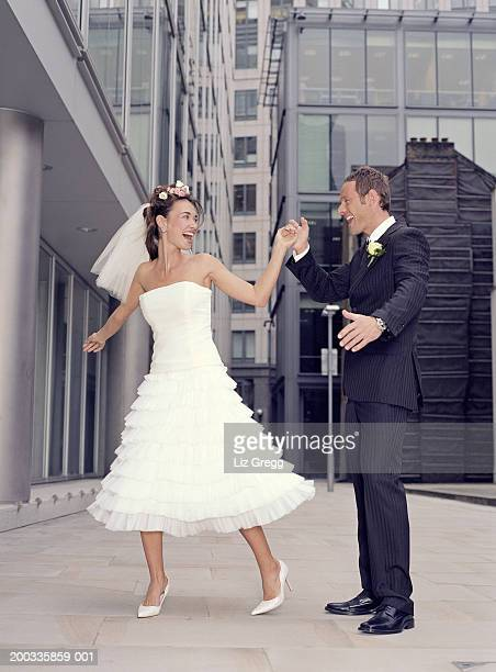 Bride and groom dancing on pavement, smiling