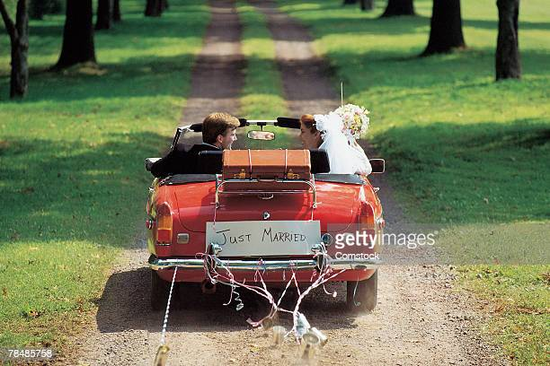 bride and groom driving away in car - newlywed stock pictures, royalty-free photos & images