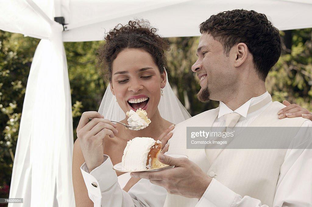Bride and groom eating wedding cake : Stockfoto