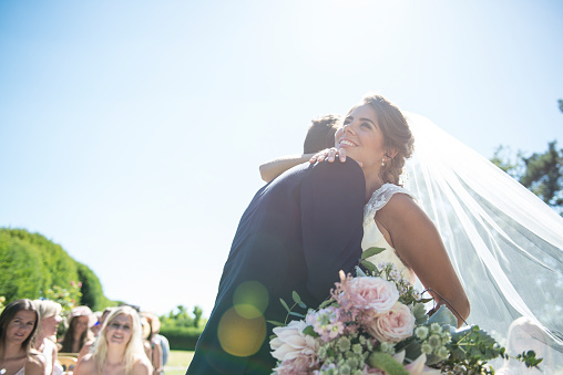 A bride and groom embrace on their wedding day - gettyimageskorea