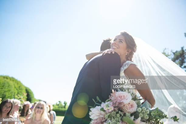 a bride and groom embrace on their wedding day - matrimonio foto e immagini stock