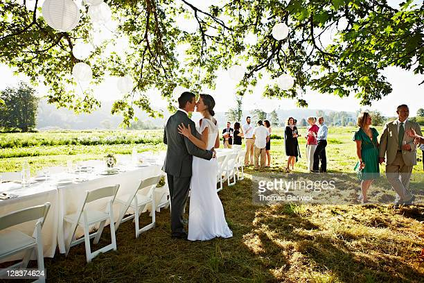Bride and groom embracing about to kiss near table