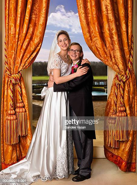 Bride and groom embracing in front of window, smiling, portrait