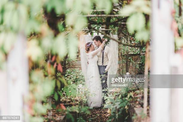Bride and groom embracing in greenhouse